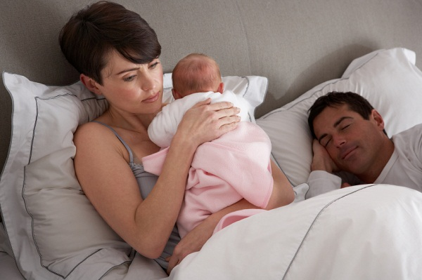 Mother Cuddling Newborn Baby In Bed At Home