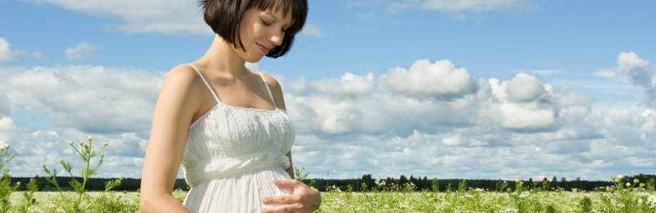 Pregnant woman smiling on a field