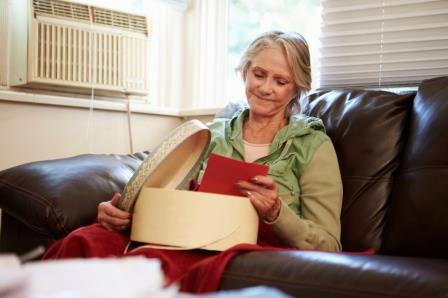 Senior Woman Keeping Warm Under Blanket With Memory Box