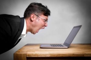 Man screaming at laptop