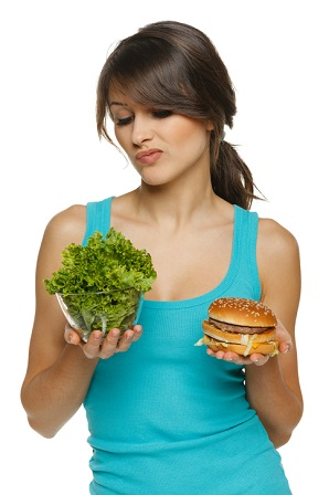 Hesitating woman making decision between healthy salad and fast food