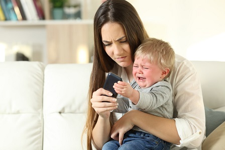 Baby tantrum fighting with his mother for a smart phone