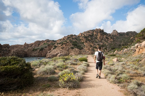 A man with a backpack is hiking along the trail coast of Sardinia in Italy
