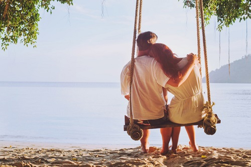 romantic holidays, honeymoon, affectionate couple on beach on swing