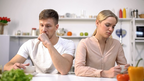 Upset couple ignoring each other at kitchen, relationship difficulties, quarrel