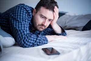 man looking at mobile phone wanting to access porn
