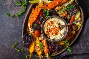 pros and cons of veganism Baked carrots, beets, zucchini and yam with hummus in a dark dish.